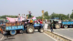 Farmers block the road in protest against the passing of agriculture reform bills in the Parliament, at Rohtak-Chandigarh National Highway, near Brahaman Bass village, in Rohtak, Haryana.